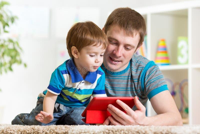 Padre feliz y su niño con PC de la tableta foto de archivo