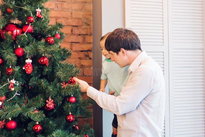 Padre feliz y su pequeño hijo que adornan el árbol de navidad en casa imágenes de archivo libres de regalías