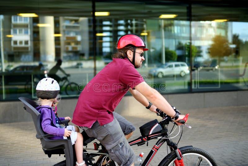 Padre feliz y su pequeño rinid de la hija del niño una bici junto foto de archivo