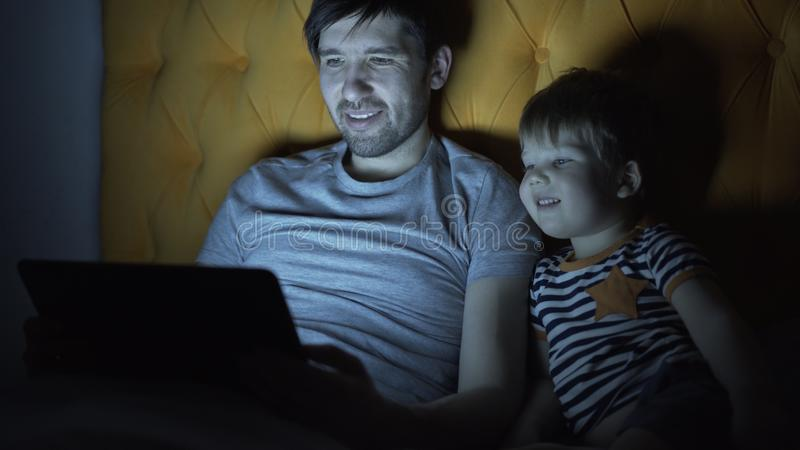 Padre giovane ed il suo film di sorveglianza del fumetto del piccolo figlio facendo uso del computer portatile mentre trovandosi  fotografia stock