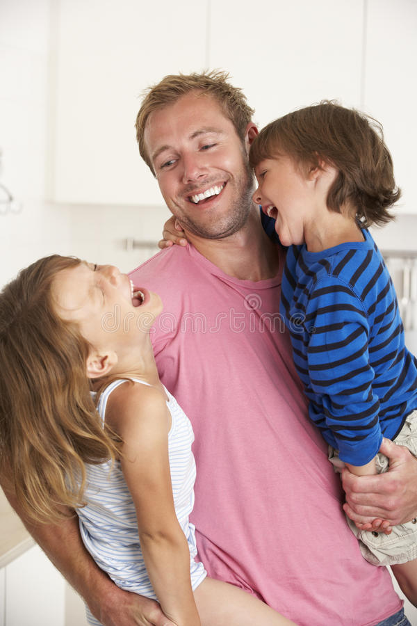 Padre Giving Children Cuddle en casa imagen de archivo