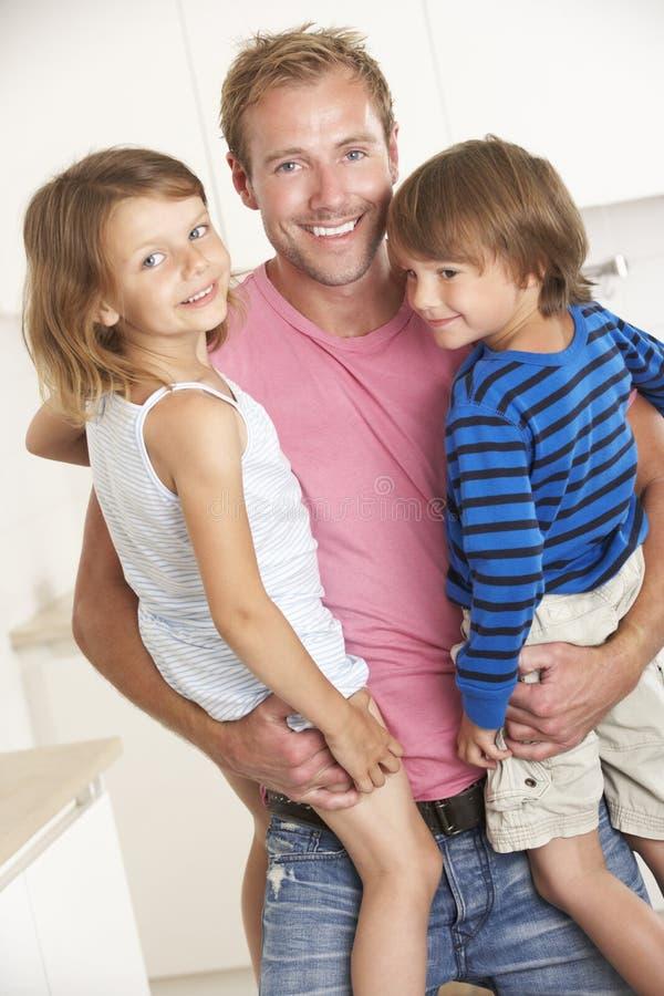 Padre Giving Children Cuddle en casa foto de archivo