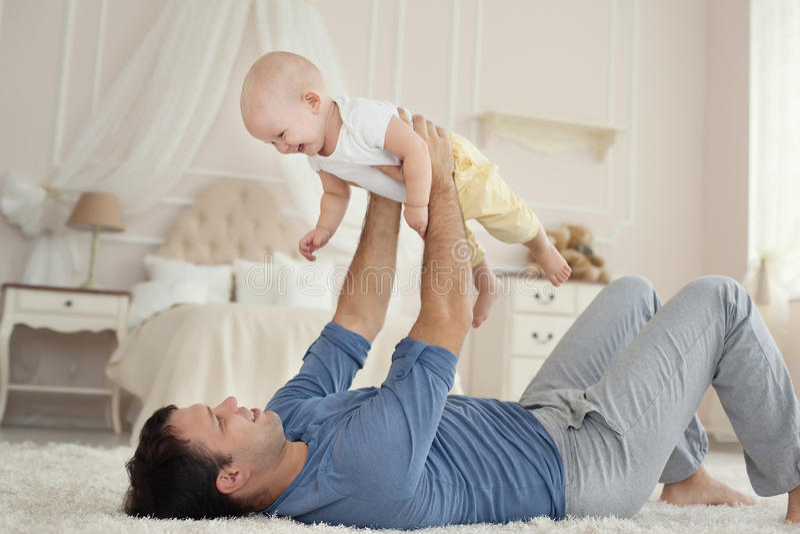 Padre hermoso joven e hijo lindo en el hogar foto de archivo