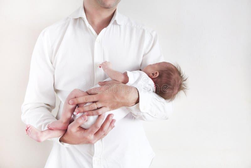 Padre hermoso que detiene a su hija recién nacida durmiente del bebé imagenes de archivo