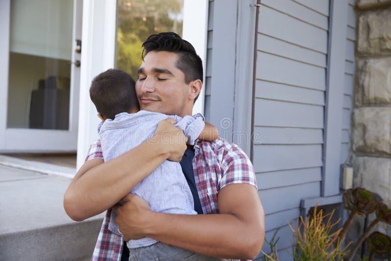Padre Hugging Son Sitting en pasos fuera del hogar imagenes de archivo