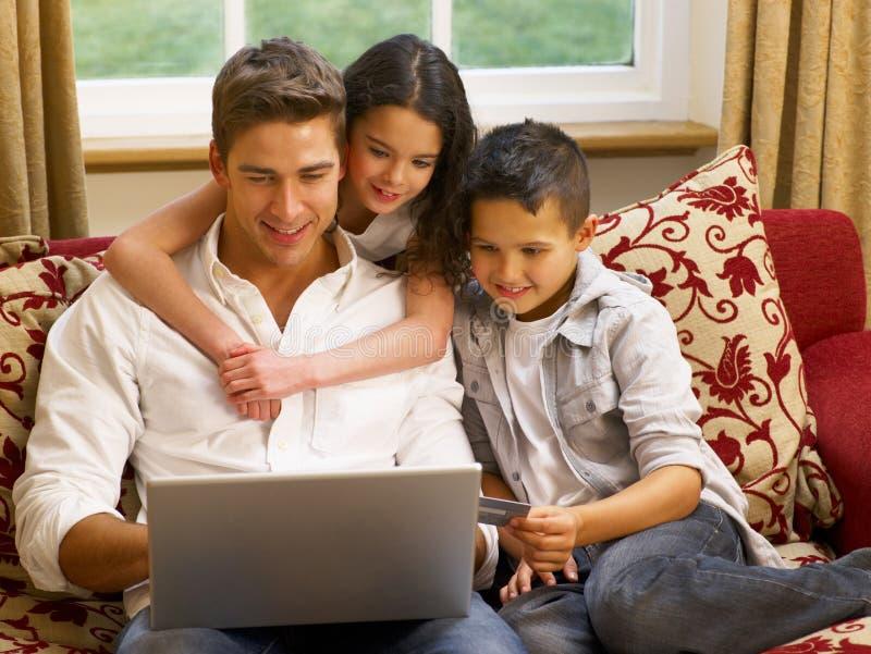 Padre ispanico e bambini che acquistano in linea fotografia stock libera da diritti
