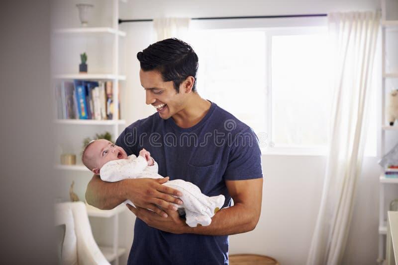 Padre ispano fiero che tiene il suo bambino di quattro mesi a casa, visto dalla entrata fotografia stock libera da diritti