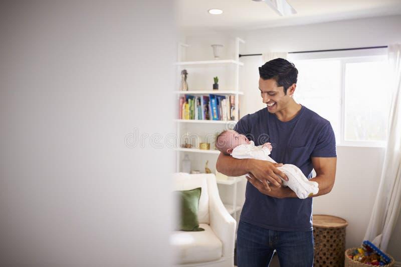 Padre ispano fiero che tiene il suo bambino di quattro mesi a casa, visto dalla entrata immagine stock