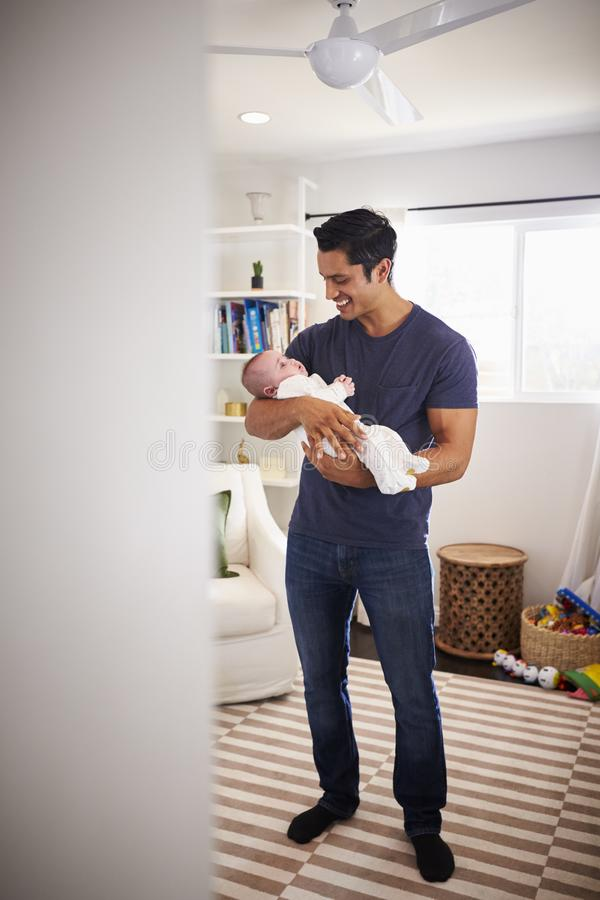 Padre ispano fiero che tiene il suo bambino di quattro mesi a casa, visto dalla entrata, verticale fotografia stock libera da diritti