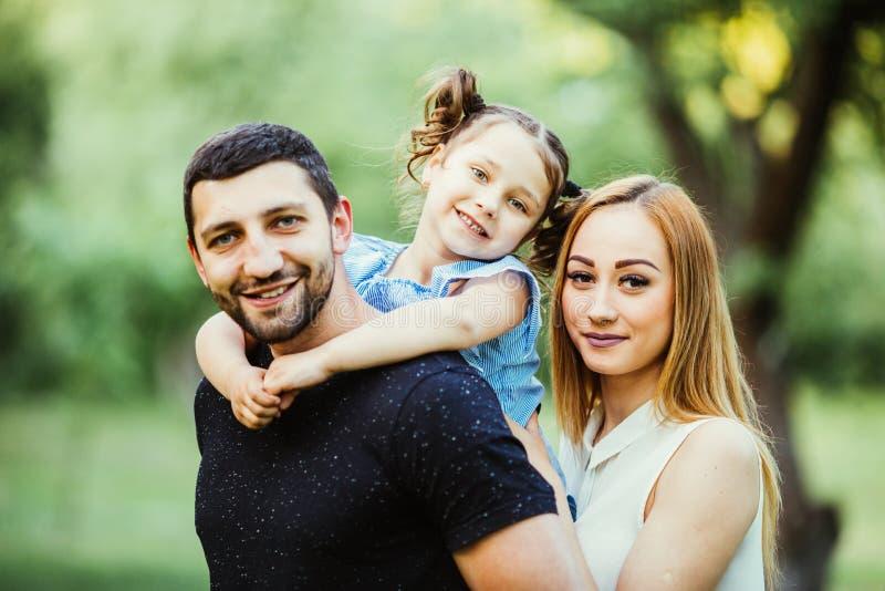 Padre joven alegre feliz de la familia, madre y pequeña hija divirtiéndose al aire libre, jugando junto en parque del verano, cam fotografía de archivo libre de regalías