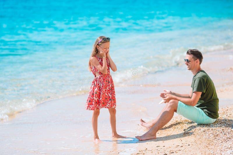 Padre joven aplicando crema solar a la nariz de la hija en la playa Protección solar imagen de archivo libre de regalías