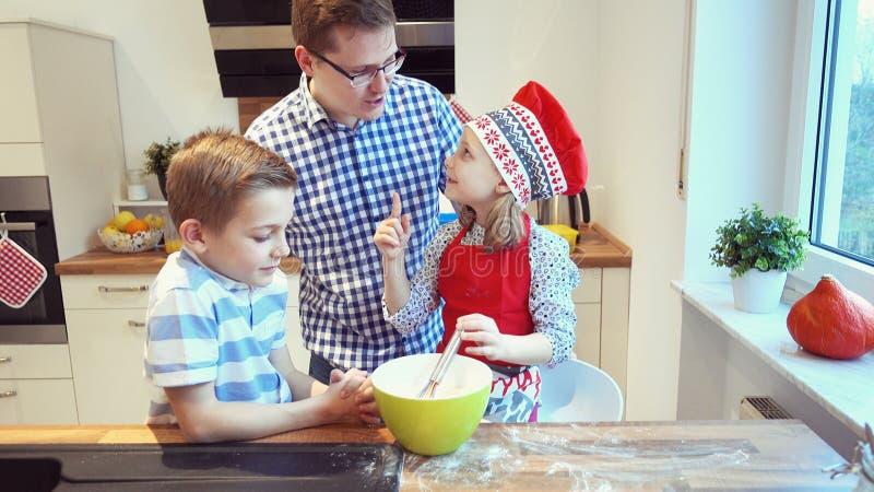Padre joven con dos niños felices que apoyan las galletas en k moderna foto de archivo