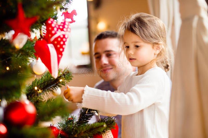 Padre joven con el daugter que adorna el árbol de navidad junto imágenes de archivo libres de regalías