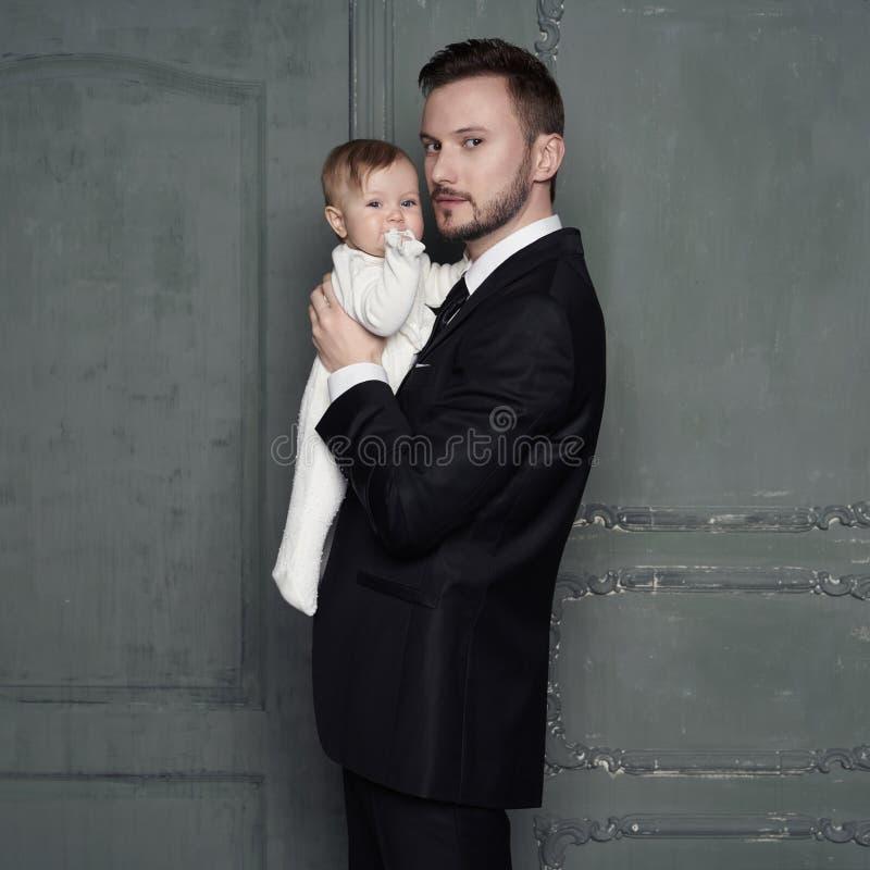 Padre joven con el peque?o beb? hermoso en sus brazos fotografía de archivo libre de regalías
