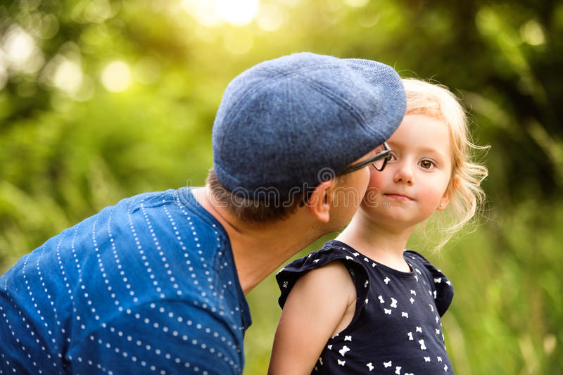 Padre joven con la hija en la naturaleza que hace su peinado foto de archivo