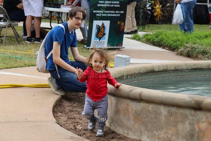 Padre joven con la hija linda del bebé de los relojes de la mochila que juega por la piscina en la demostración Tulsa Oklahoma lo imagen de archivo