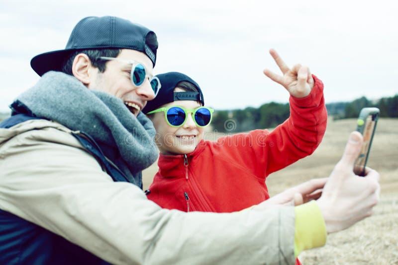 Padre joven con su hijo que tiene exterior de la diversi?n en el campo de la primavera, familia feliz que sonr?e, gente de la for imagen de archivo