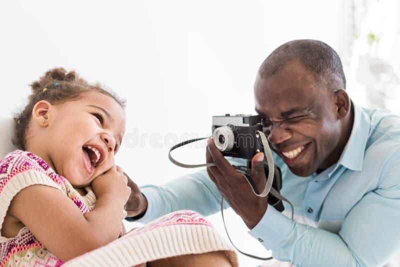 Padre joven con su pequeña hija linda que toma imágenes de uno a en una cámara vieja del vintage imágenes de archivo libres de regalías