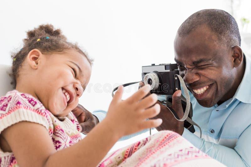 Padre joven con su pequeña hija linda que toma imágenes de uno a en una cámara vieja del vintage imagen de archivo