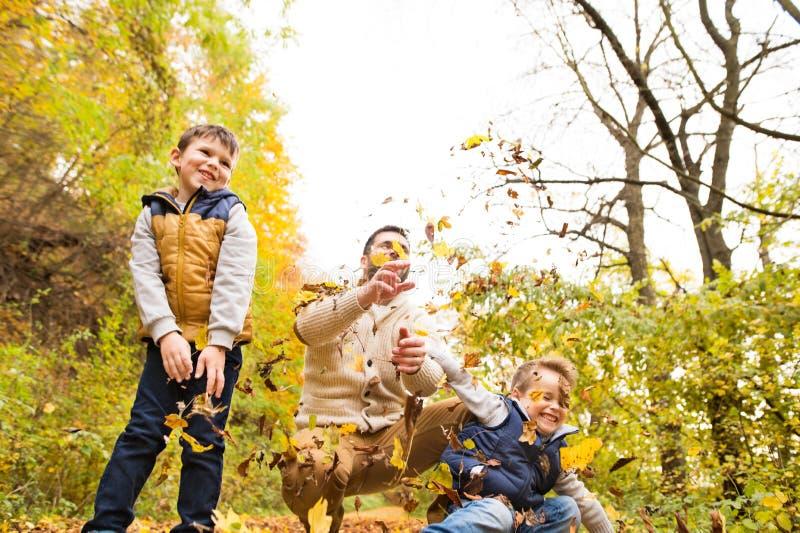 Padre joven con sus hijos en bosque del otoño imágenes de archivo libres de regalías