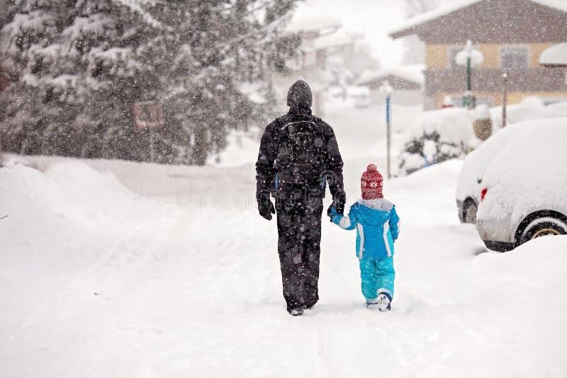 Padre joven e hijo, caminando de común acuerdo abajo de la calle imagen de archivo libre de regalías