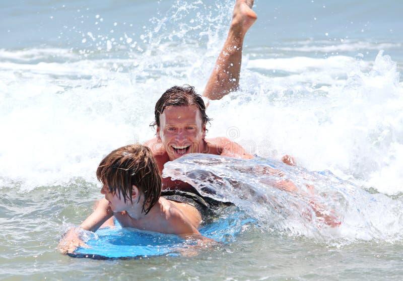 Padre joven e hijo que aprenden practicar surf foto de archivo libre de regalías