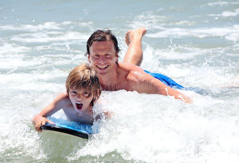 Padre joven e hijo que aprenden practicar surf foto de archivo