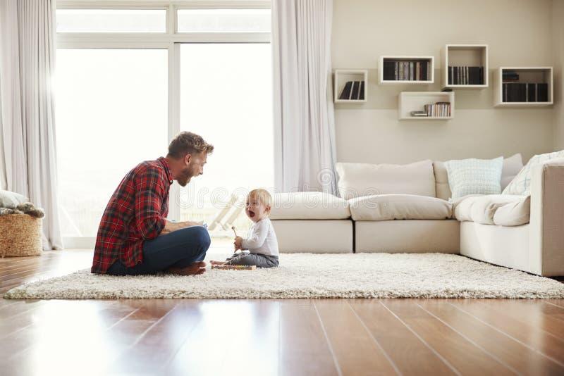 Padre joven e hijo que juegan junto en su salón imagenes de archivo