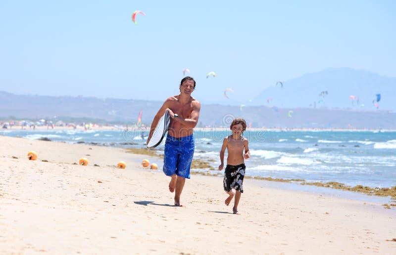 Padre joven e hijo que se ejecutan a lo largo de la playa con la tabla hawaiana fotos de archivo libres de regalías