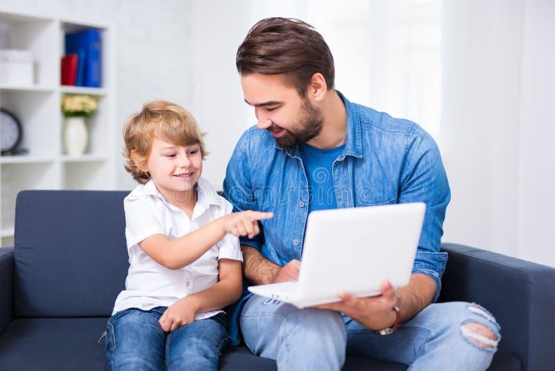 Padre joven e hijo que se sientan en el sofá con el ordenador portátil imagen de archivo libre de regalías