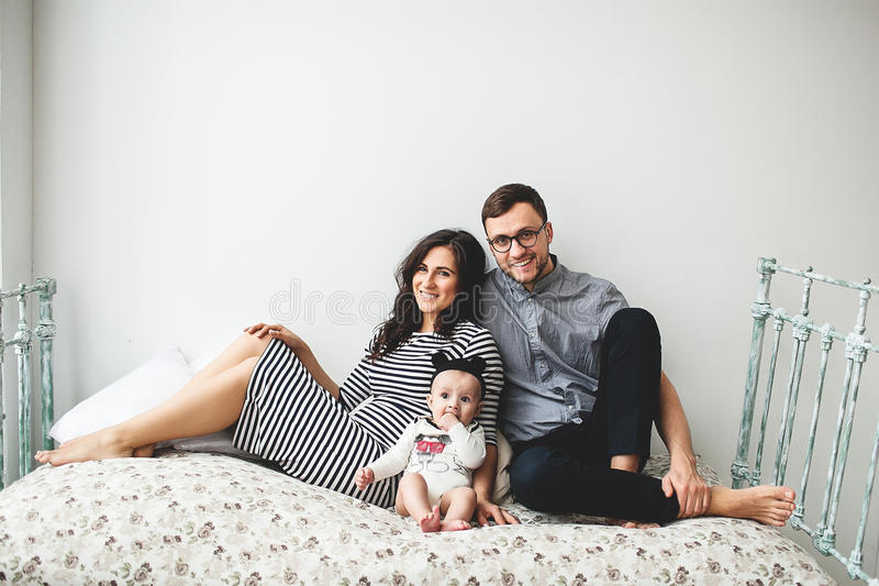 Padre joven feliz, madre y bebé lindo mintiendo en cama rústica foto de archivo libre de regalías