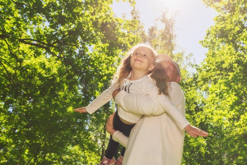 Padre joven feliz plauing con el ni?o afuera en parque foto de archivo