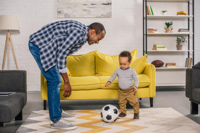 padre joven feliz que mira al pequeño hijo sonriente que juega con el balón de fútbol fotografía de archivo libre de regalías