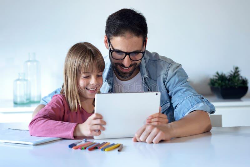 Padre joven hermoso con su pequeña hija que usa ellos tableta digital en casa fotos de archivo libres de regalías