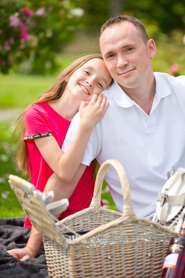 Padre joven hermoso que se sienta en una tela escocesa en un parque verde con su pequeña hija bonita con una cesta de mimbre para fotografía de archivo