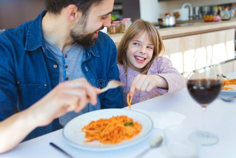 Padre joven hermoso y su hermoso divirtiéndose mientras que come las pastas con la salsa de tomate para el almuerzo en la cocina fotos de archivo