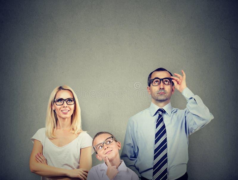 Padre joven pensativo de la madre de la familia y su niño que miran para arriba de comtemplación foto de archivo