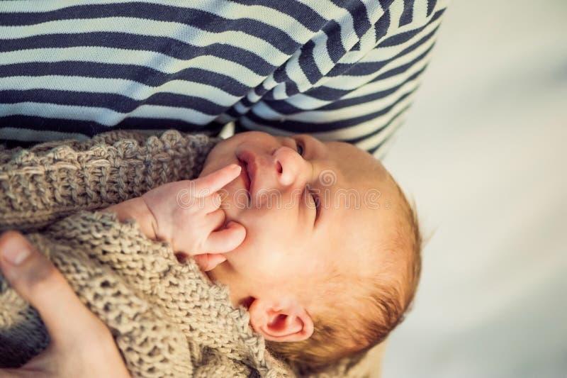 Padre joven que detiene a su hijo recién nacido del bebé en sus brazos fotos de archivo