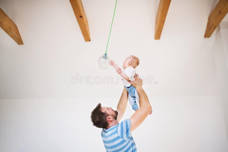 Padre joven que detiene a un hijo del bebé bajo techo en casa fotografía de archivo libre de regalías