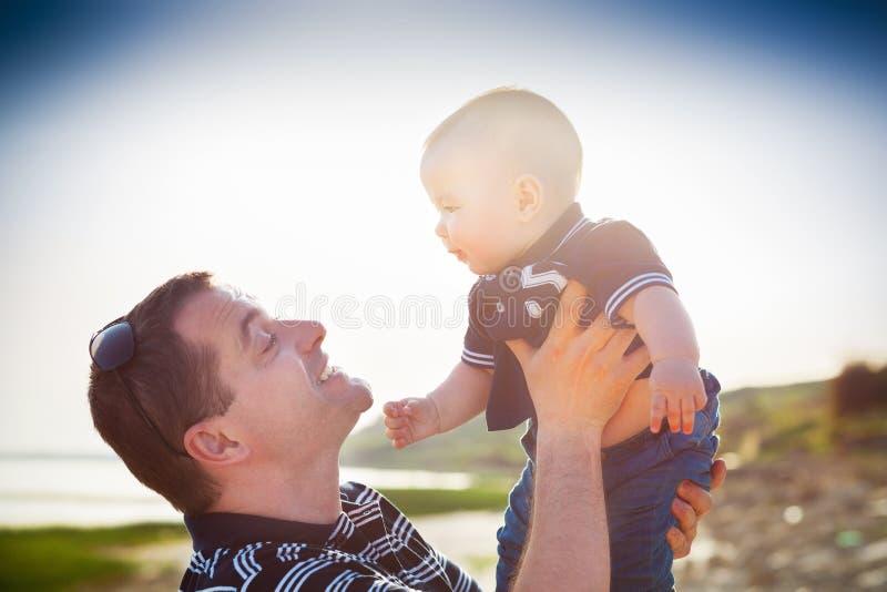 Padre joven que juega con el hijo del bebé como en la playa imagen de archivo