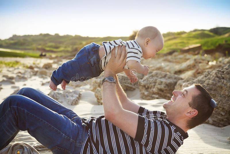 Padre joven que juega con el hijo del bebé como mintiendo en la playa fotos de archivo libres de regalías