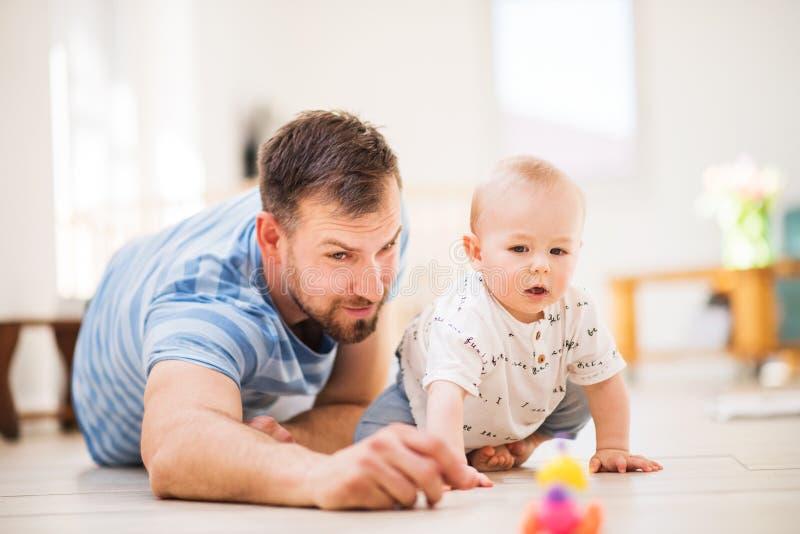 Padre joven que juega con un hijo del bebé en casa fotografía de archivo libre de regalías