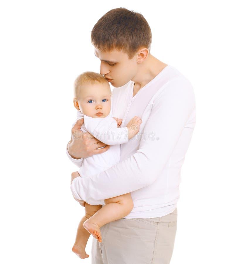 Padre joven que lleva a cabo encendido las manos y que besa al bebé imagen de archivo libre de regalías