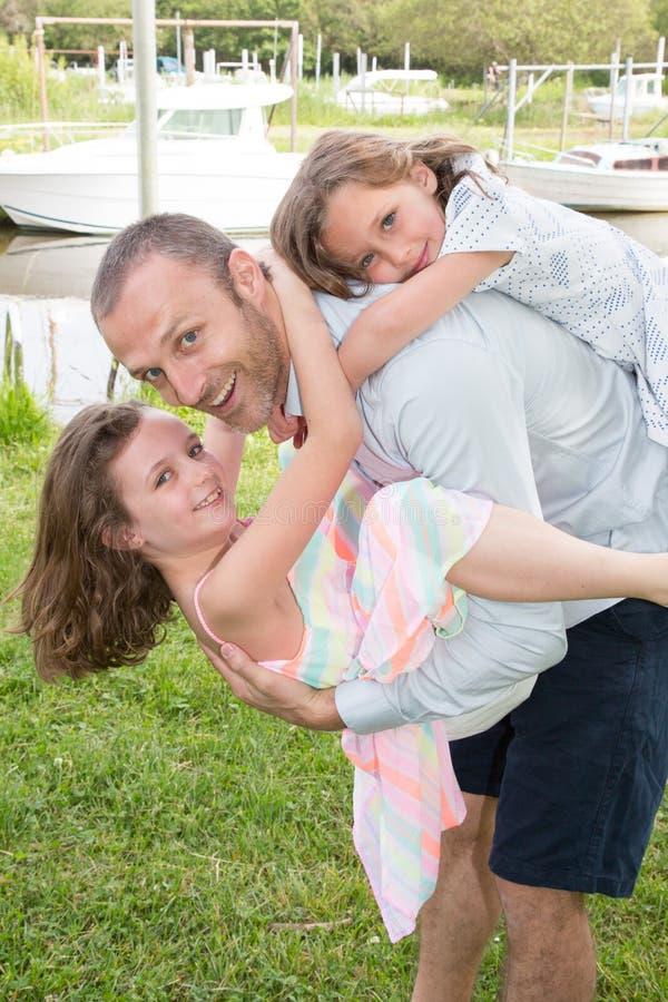 Padre joven que lleva a una hija en el suyo parte posterior y otro niño de la muchacha en transporte por ferrocarril del frente fotografía de archivo libre de regalías