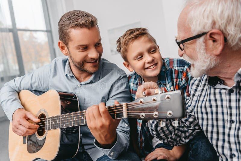 Padre joven que toca la guitarra mientras que son el pequeños hijo y abuelo imágenes de archivo libres de regalías