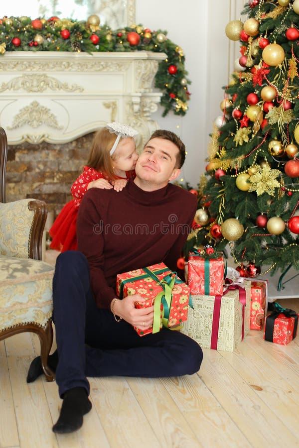 Padre joven sittling con la chimenea adornada cercana y el árbol de navidad de la pequeña hija, guardando presentes imagen de archivo libre de regalías