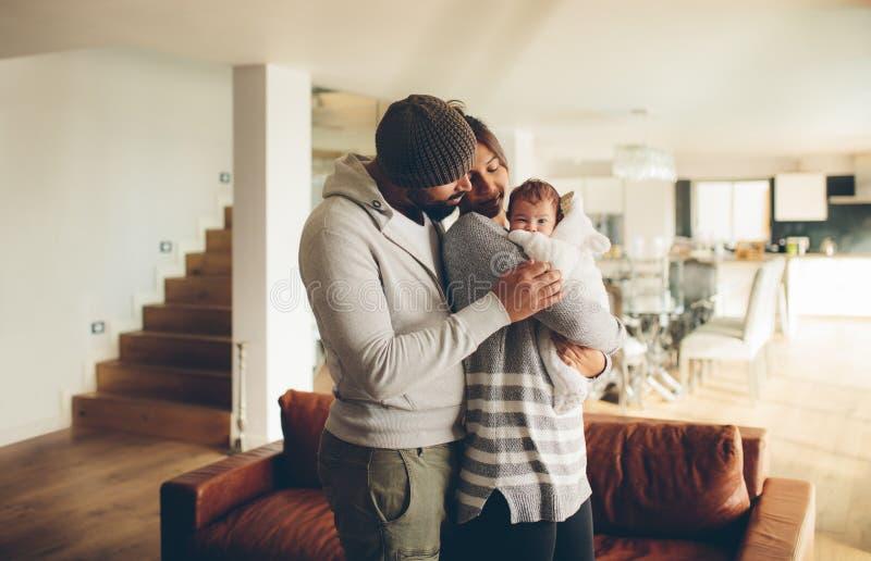 Padre joven y madre que celebran a su bebé imagen de archivo