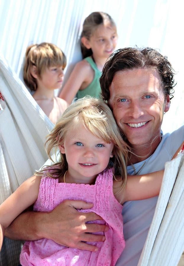 Padre joven y niños que se sientan en una hamaca el vacaciones imagen de archivo