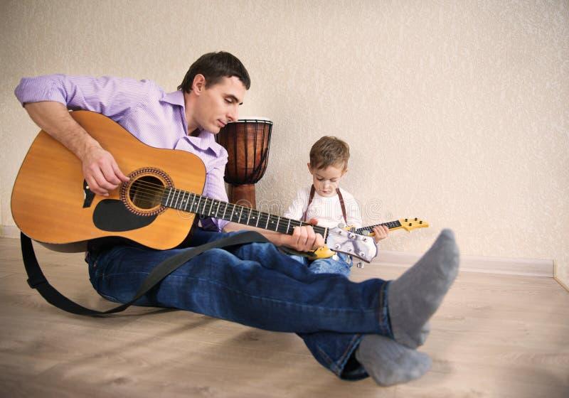 Padre joven y pequeño hijo que tocan la guitarra fotografía de archivo