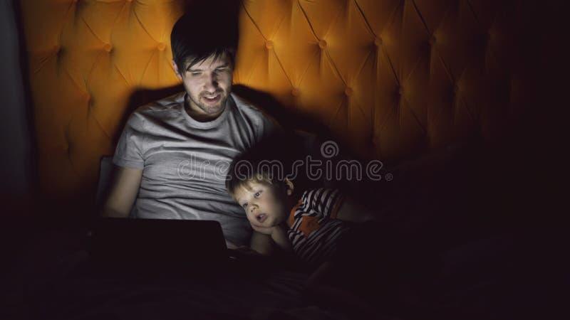 Padre joven y su película de observación de la historieta del pequeño hijo usando la tableta y hablar mientras que miente en cama foto de archivo libre de regalías